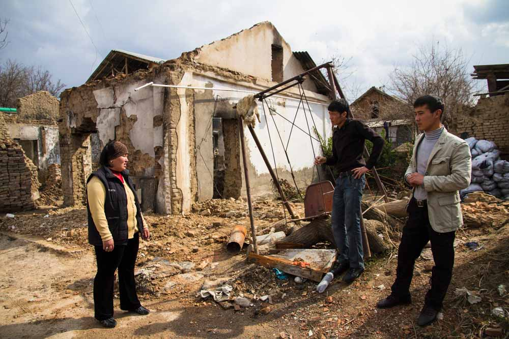 Eine kirgisische Familie vor ihrem zerstörten Haus in Osch, ein Jahr nach den ethnischen Ausschreitungen im Sommer 2010 (Foto: Edda Schlager)